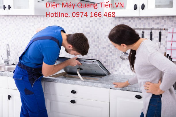 Woman Looking At Serviceman In Uniform Fixing Induction Stove In The Kitchen